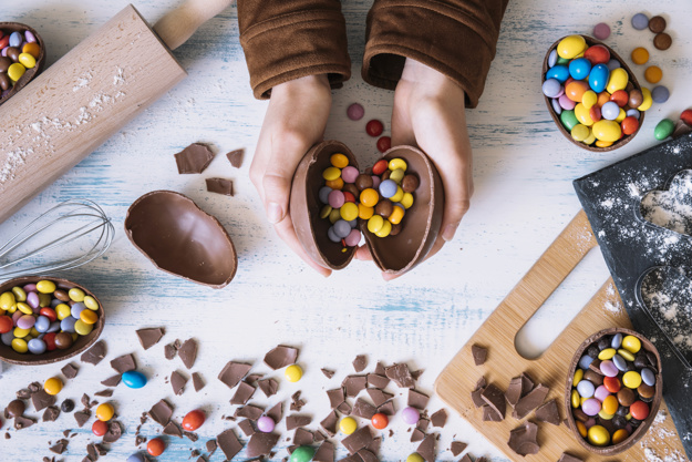 cortar-as-maos-abrindo-ovo-de-chocolate_23-2147748721